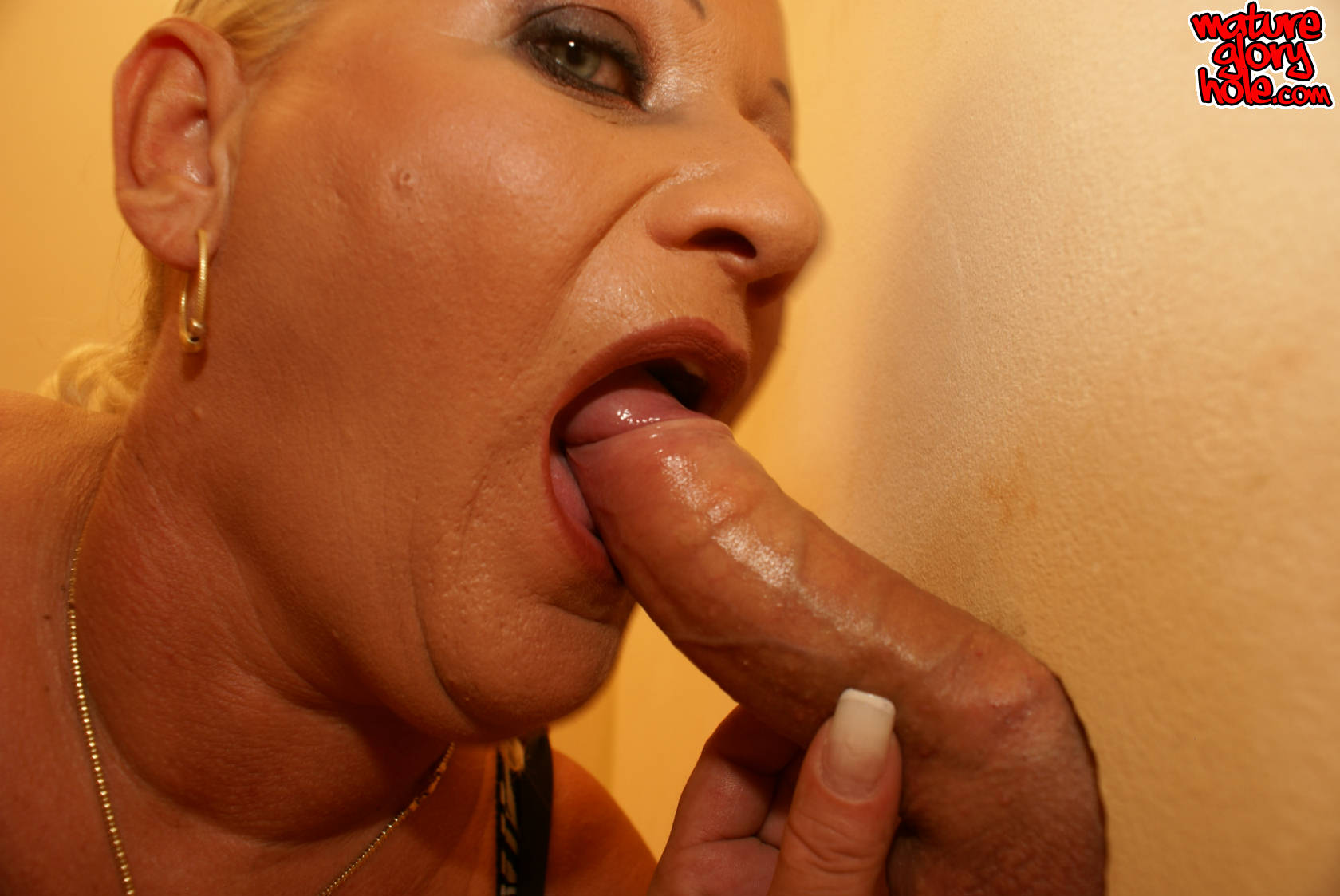 Busty Mom gets a big cock surprise through a hole in a toilet